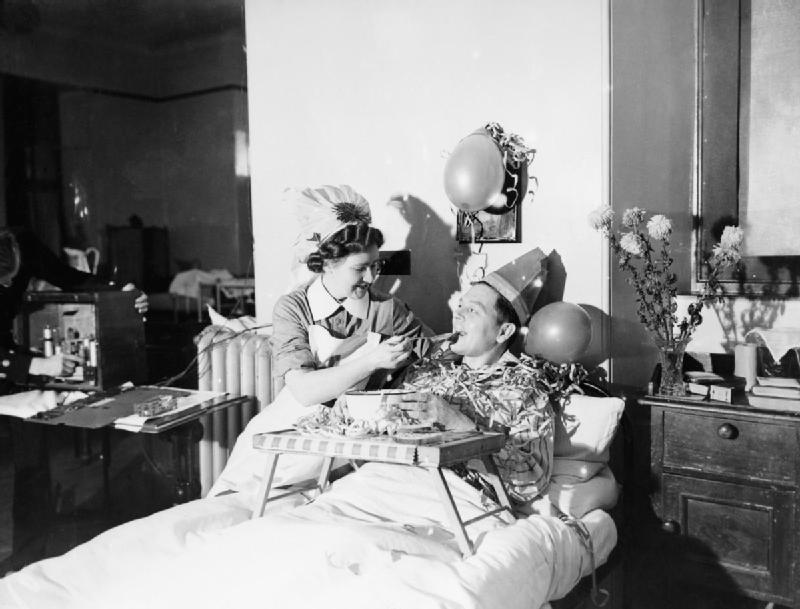 A_nurse_feeds_a_patient_with_a_spoonful_of_Christmas_pudding_at_a_naval_hospital_at_Kingseat_in_Scotland,_December_1941._A6486